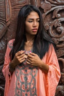 Piękny model azjatycki w różowej sukience boho pozuje na drewnianej ścianie ozdobnej.