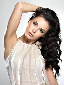 Piękny model brunetka z długimi kręconymi brązowymi włosami. ładny model pozuje w studio.