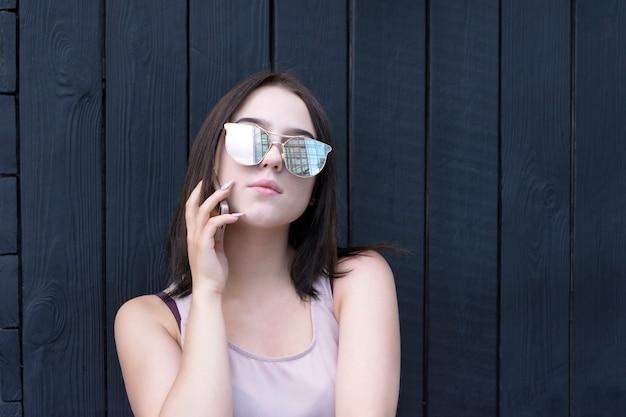 Piękny model cieszący się rozmową telefoniczną w okularach przeciwsłonecznych