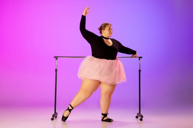 Piękny model kaukaski plus size ćwiczący taniec baletowy na fioletowo-różowym tle studia w świetle neonu. pojęcie motywacji, włączenia, marzeń i osiągnięć. warto być baletnicą.