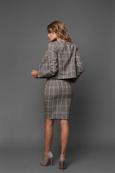 Piękny model kobiety z idealnym ciałem i seksownymi nogami w formalne ubrania na szarym tle. młoda kobieta w modny garnitur i buty na obcasie, pozowanie z plecami na szarym tle.