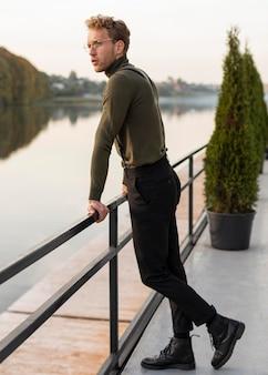Piękny model mężczyzna patrząc na widok z boku jeziora