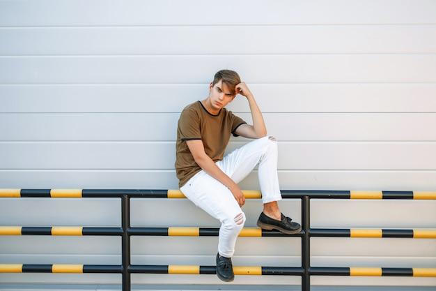 Piękny model mężczyzna w modnych ubraniach i skórzanych czarnych butach siedzi w pobliżu szarej ściany
