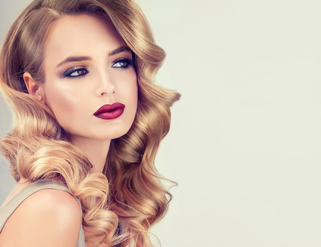 Piękny model o długiej, gęstej, kręconej fryzurze wieczorowej i wyrazistym makijażu z przydymionymi powiekami i czerwoną szminką. sztuka fryzjerska, pielęgnacja włosów, kosmetyki i kosmetyki.