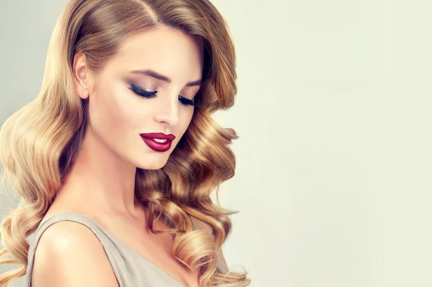 Piękny model o długiej, gęstej, kręconej wieczorowej fryzurze i wyrazistym makijażu z długimi czarnymi rzęsami i czerwoną szminką. sztuka fryzjerska, produkty do pielęgnacji i pielęgnacji włosów.