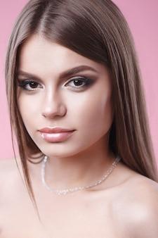 Piękny model o jasnym makijażu, z czystą skórą i naszyjnikiem na różowym tle