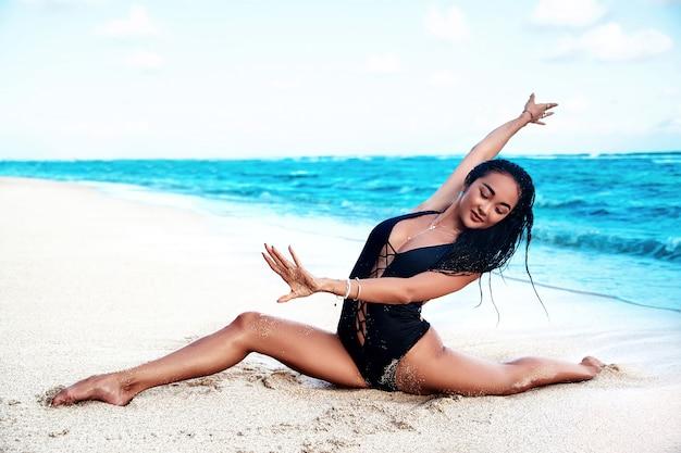 Piękny model opalonej kobiety rasy kaukaskiej z ciemnymi długimi włosami w czarnym elastycznym stroju kąpielowym do jogi robi rozszczepiony i pozuje na letniej plaży z białym piaskiem na niebieskim niebie i oceanie
