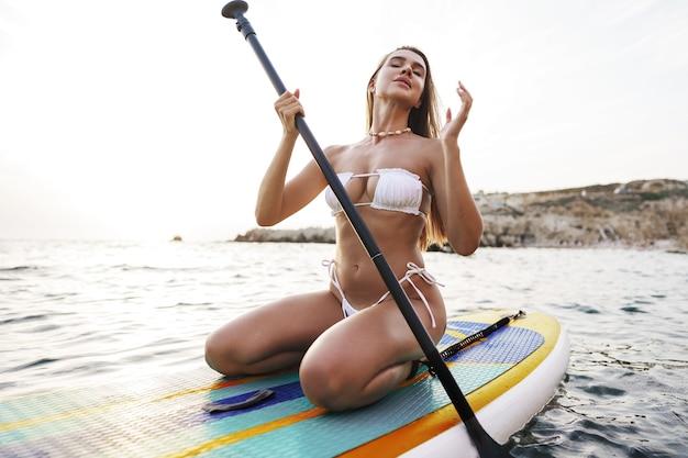 Piękny model paddlbording relaks w morzu z czystą wodą