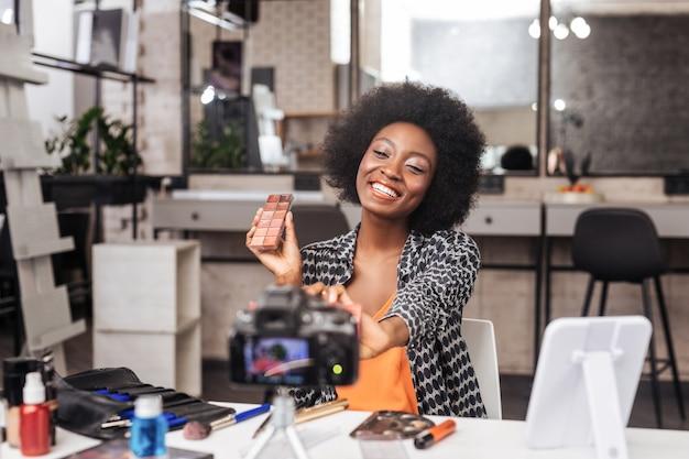 Piękny model. piękna ciemnoskóra kobieta z kręconymi włosami, uśmiechnięta jasno
