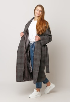 Piękny Model Pozowanie W Długim Brązowym Płaszczu Na Białym Tle. Strzał Studio. Koncepcja Reklamy Odzieży. Premium Zdjęcia