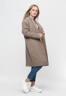 Piękny model pozuje w długim brązowym płaszczu