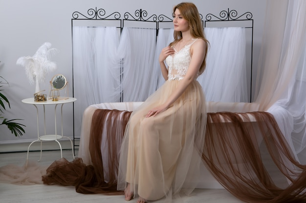 Piękny model pozuje w łazience w seksownym szlafroku.