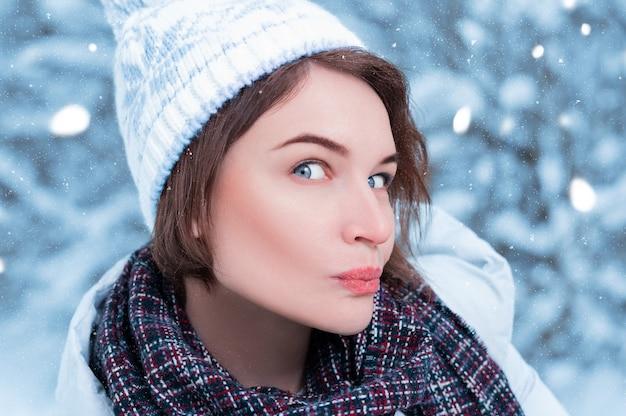 Piękny model robi zabawną, zaskoczoną minę. zimowy las. ciepłe ubrania i koncepcja świąteczne zakupy. różne środki przekazu