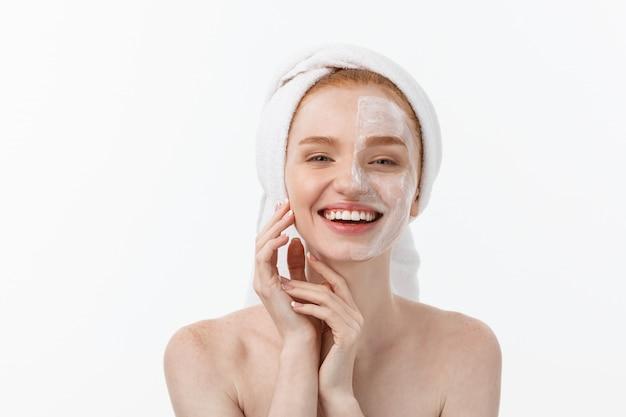 Piękny model stosujący krem kosmetyczny na twarz na białym tle.