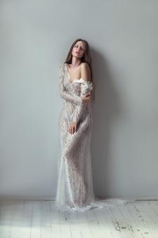 Piękny model ubrany w białą koronkową sukienkę pozuje w jasnym pokoju