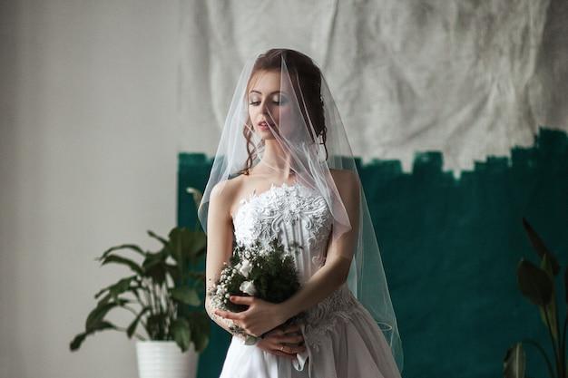 Piękny model ubrany w białą koronkową sukienkę pozuje w wewnętrznym studio