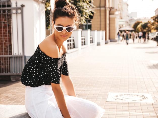 Piękny model uśmiechający się ubrany w eleganckie letnie ubrania. seksowna beztroska dziewczyna siedzi na ulicy. modny nowoczesny bizneswoman w okularach przeciwsłonecznych, zabawy