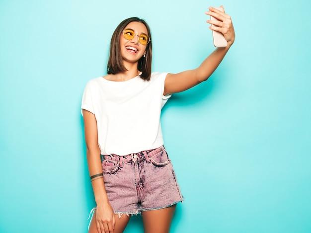 Piękny model uśmiechający się ubrany w letnie ubrania hipster. seksowna beztroska dziewczyna pozuje w studiu blisko błękit ściany w cajgów skrótach. modna i śmieszna kobieta robi selfie autoportretowi zdjęcia na smartfonie