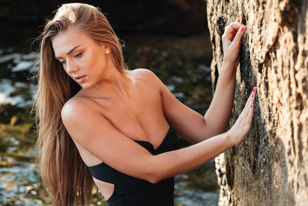 Piękny model w stroju kąpielowym. tak seksowna dziewczyna. niedaleko morza. blisko skał rock