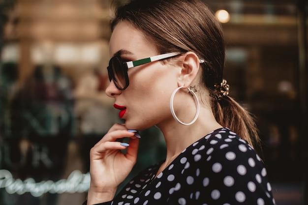 Piękny model wygląda brunetka kobieta ubrana w białą sukienkę w czarne kropki jest podczas przebudzenia na tle ulicy miasta ze stylowymi torbami w dłoni.