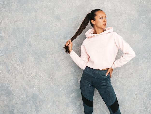 Piękny model z idealnie opalonym ciałem. kobieta stanowiąca studio w pobliżu szarej ściany. trzyma w ręku ogon włosów
