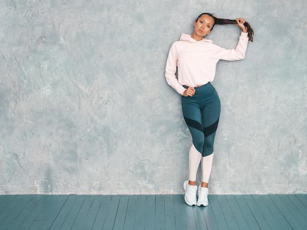 Piękny model z idealnie opalonym ciałem. kobieta stanowiąca studio w pobliżu szarej ściany. trzyma włosy w ręku
