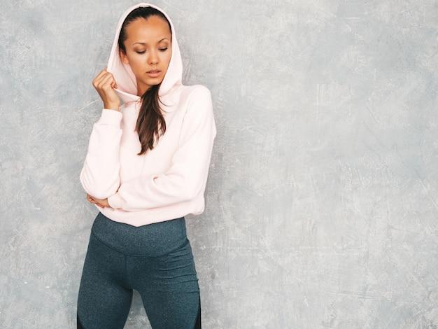 Piękny model z idealnie opalonym ciałem. kobieta stanowiąca studio w pobliżu szarej ściany w kapturze