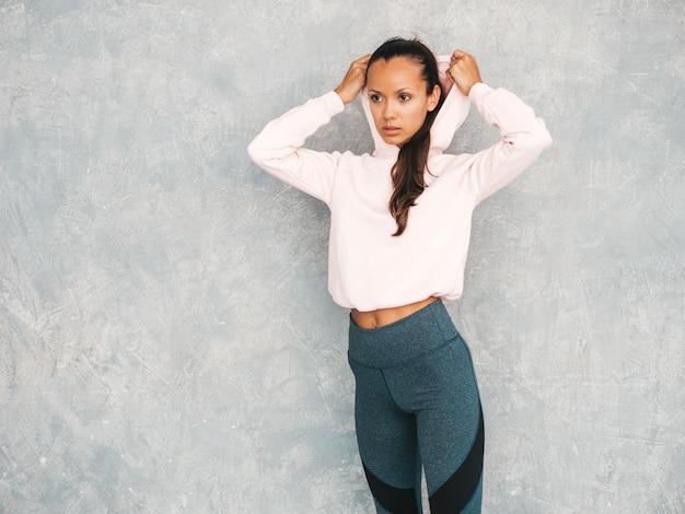 Piękny model z idealnie opalonym ciałem. kobieta stanowiąca studio w pobliżu szarej ściany