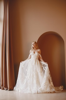 Piękny model z makijażem ślubnym i fryzurą w koronkowej sukience małżeńskiej.