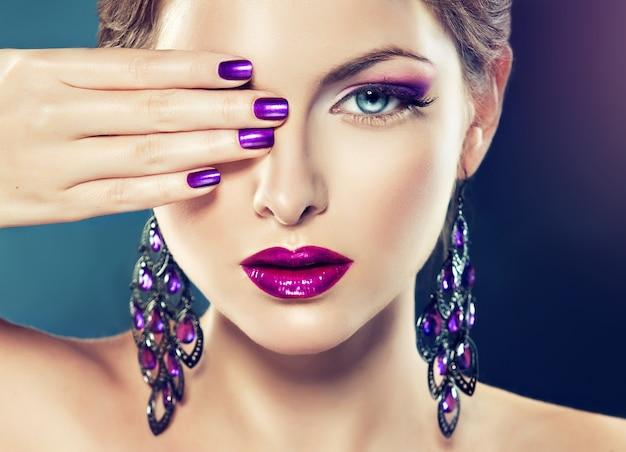 Piękny model z modnym makijażem i fioletowym manicure na paznokciach. na niej duże orientalne kolczyki. biżuteria kosmetyczna i manicure.