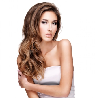 Piękny model z pięknymi długimi włosami i makijażem, pozowanie w studio. na białym tle