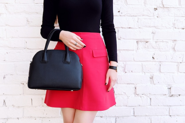 Piękny modny strój, czerwona spódnica i czarna duża skórzana torba w dłoni. stylowy dodatek