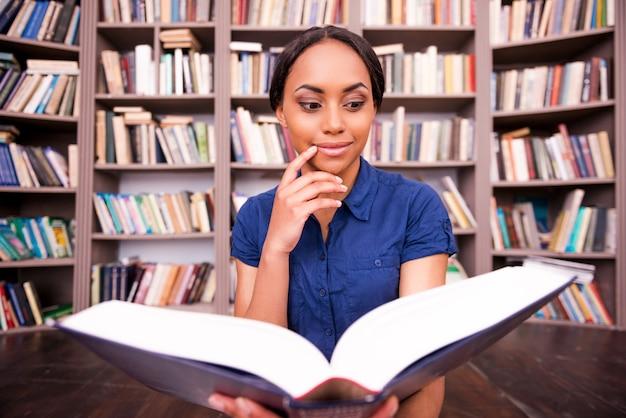 Piękny mól książkowy. rozważna afrykańska studentka czytająca książkę i trzymająca rękę na brodzie, siedząc na podłodze w bibliotece