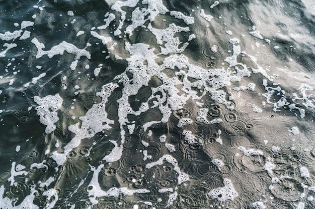 Piękny morski widok na linię wybrzeża morskiego z czystą falującą wodą na piaszczystej plaży w słoneczny dzień jako naturalne tło