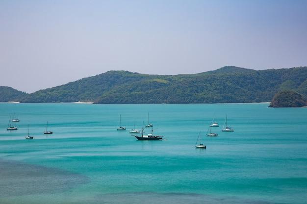 Piękny morze z łódkowatą i zieloną górą na tle