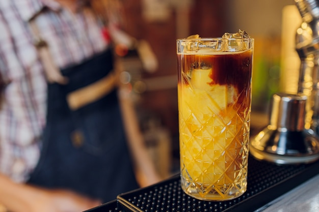 Piękny mrożony kieliszek koktajlowy z lodem, miętą i ananasem na ciemnym drewnianym blacie barowym, jasne tło bokeh.