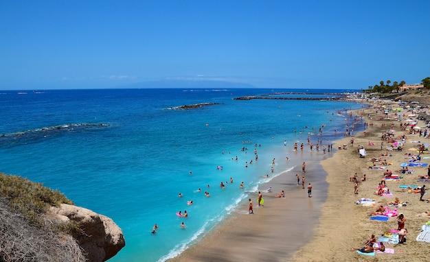 Piękny nabrzeżny widok el duque plaża w costa adeje, tenerife, wyspy kanaryjska, hiszpania. lato wakacje lub podróży pojęcie.