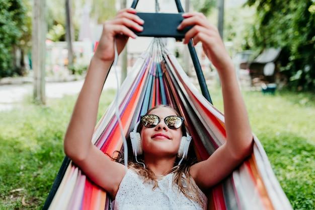 Piękny nastolatek dziewczyny lying on the beach na kolorowym hamaku przy ogródem. słuchanie muzyki na telefonie komórkowym i zestawie słuchawkowym oraz uśmiechanie się. zrelaksować się i bawić na świeżym powietrzu