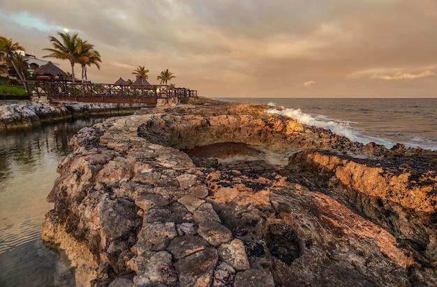 Piękny naturalny basen na skalistym wybrzeżu o zachodzie słońca w puerto aventuras w meksyku.