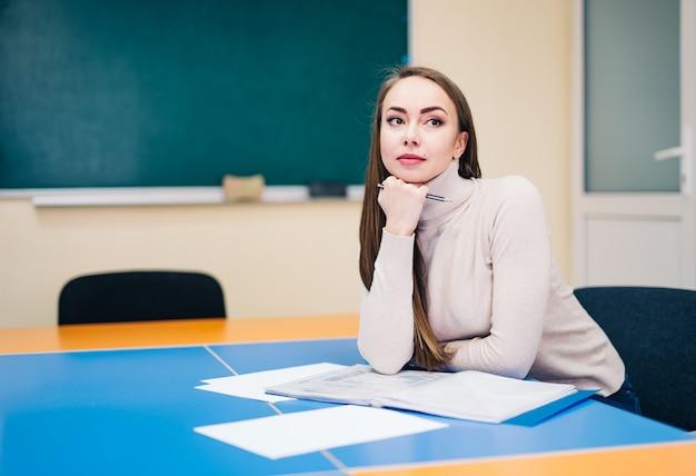 Piękny nauczyciel siedzi w klasie