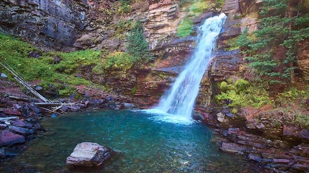 Piękny niebieski i turkusowy wodospad w kanionie skalnym