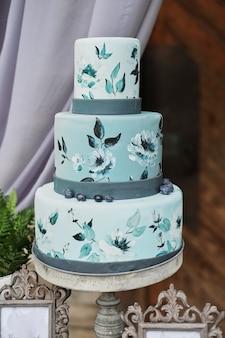 Piękny niebieski trzypoziomowy tort ozdobiony kwiatami na stojaku, na stoliku weselnym.