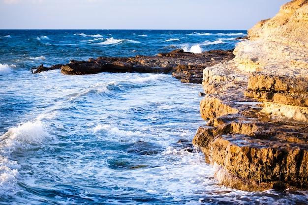 Piękny niebieski zachód słońca i woda kamienie na skalistym wybrzeżu morza czarnego na krymie w letni dzień