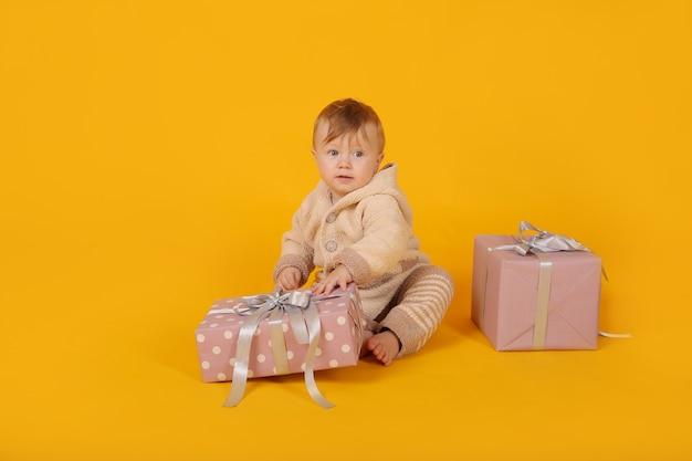 Piękny niebieskooki chłopiec w ciepłym garniturze z dzianiny z pudełkami prezentowymi na żółtym tle