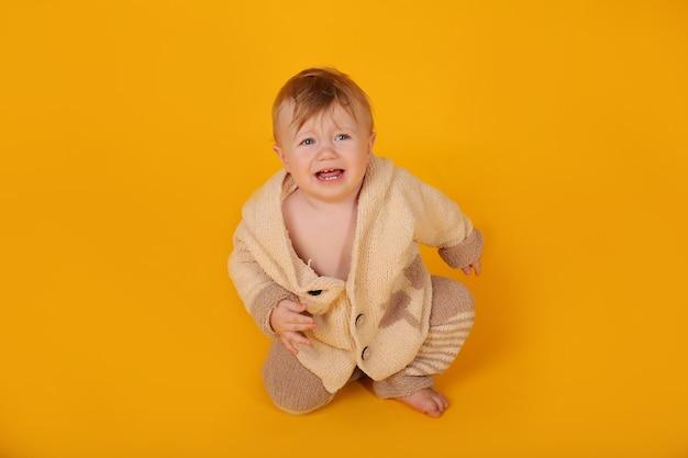 Piękny niebieskooki chłopiec w dzianinowym beżowym ciepłym garniturze na żółtym tle