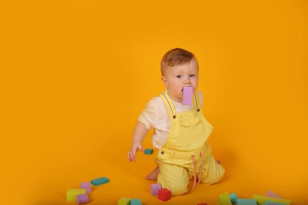 Piękny niebieskooki chłopiec w żółtym garniturze bawi się kolorowymi zabawkamiżółty