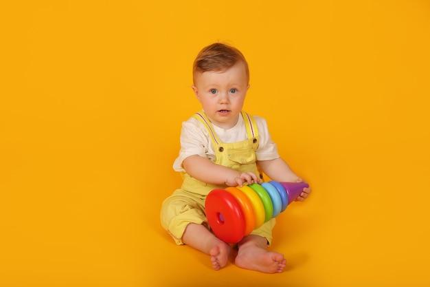 Piękny niebieskooki chłopiec w żółtym garniturze bawi się wielokolorową zabawkową piramidą