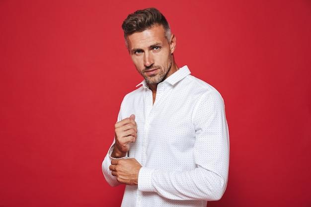 Piękny nieogolony mężczyzna 30s w białej koszuli na czerwonym tle