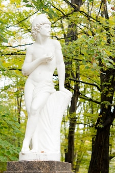 Piękny, nieskazitelny biały posąg ogrodowy przedstawiający klasycznego greckiego lub rzymskiego boga na kamiennym cokole wśród drzew