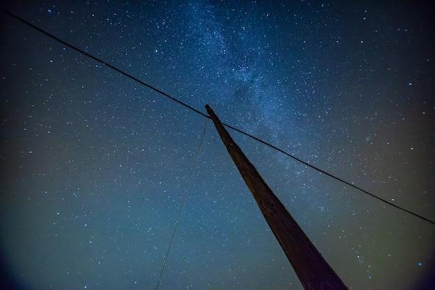 Piękny nocny krajobraz nieba z gwiazdami i słupem elektrycznym
